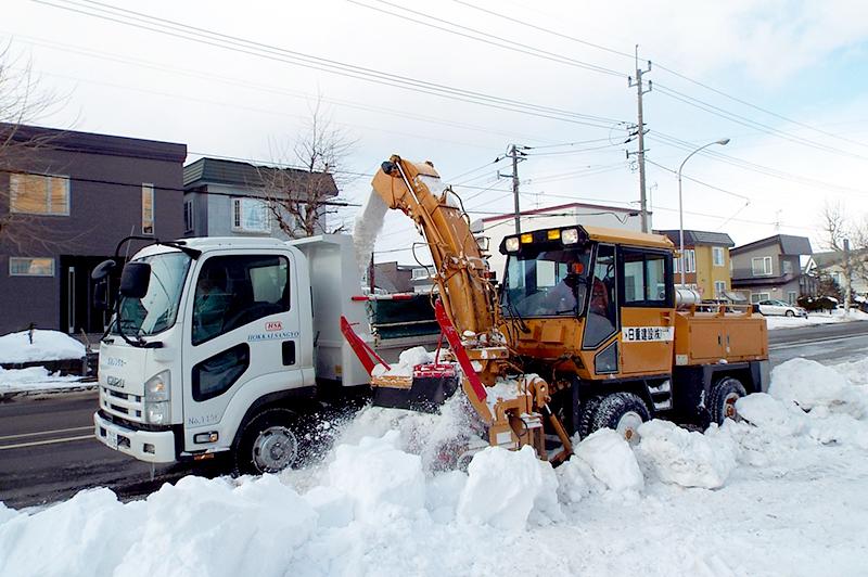 歩道の排雪を行うロータリ除雪車と排雪トラック