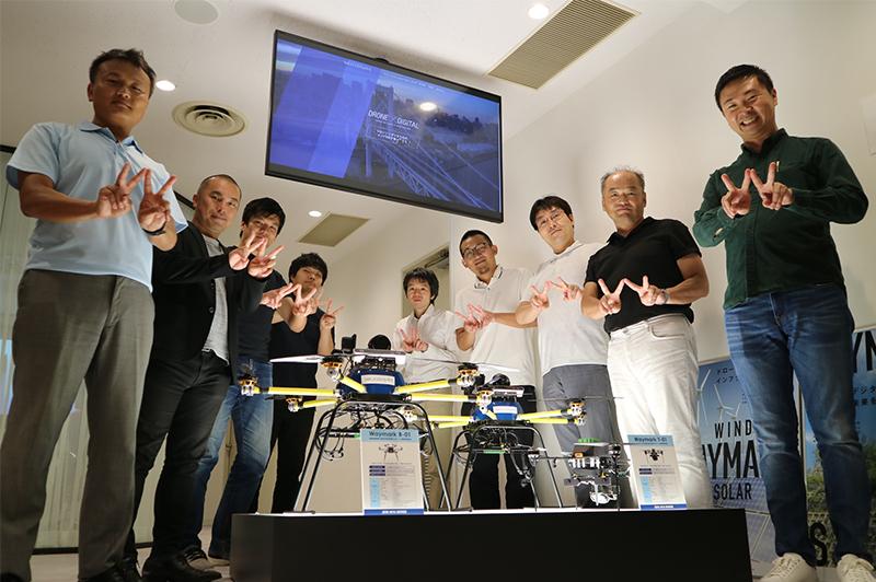 ジャパン・インフラ・ウェイマークの社員とともにポーズを決める春田さん(左端)。ハンドサインは「ウェイマーク」の「W」。