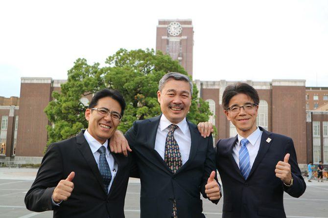 京都大学百周年時計台記念館をバックに、笑顔で肩を組む藤井聡氏(中央)、見坂茂範氏(右)、岡村正典氏