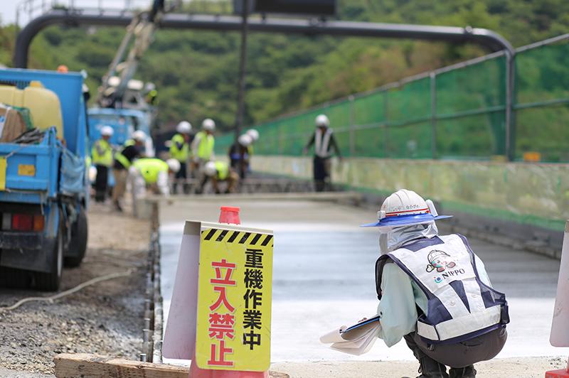 コンクリート舗装の平坦性などの仕上がりを確認する中川さん